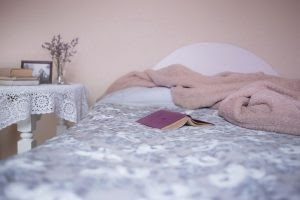 Bed ready for sleep, with book and blanket.