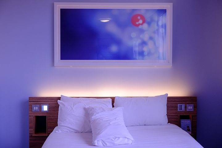 Bedroom with bed in white linen and blue light: sleep disorders.